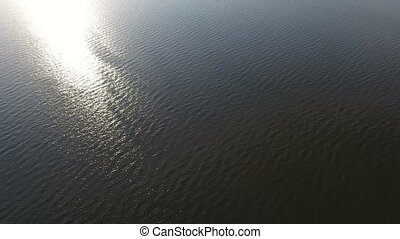 Aerial shot of the sparkling Black Sea waters and a sun path at sunset in summer