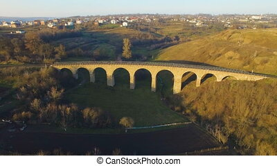 aerial shot of the stone railway bridge in sunset with interesting shadow 4k