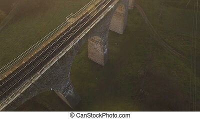 aerial shot of the stone railway bridge in sunset with...