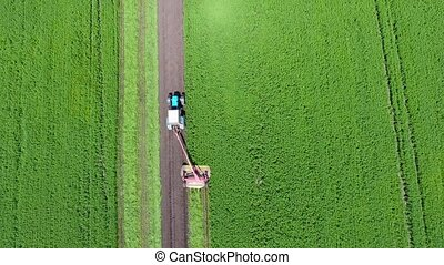 Aerial shot of tractor spraying field