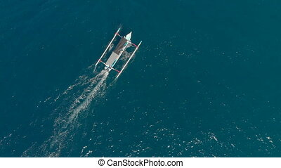 Aerial shot of traditional Balinese boats in an open sea. Travel to Indonesia concept