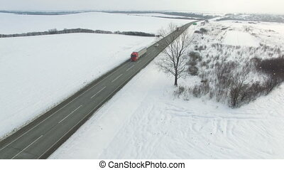 Aerial shot of truck and cars driving winter road in snowy field.