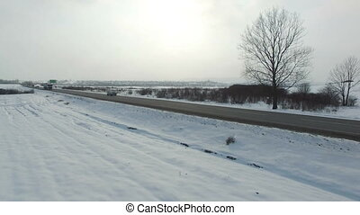 Aerial shot of truck driving winter road in snowy field.
