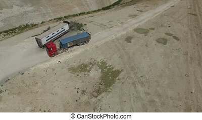 Aerial shot of truck with garbage is parking on junkyard for unloading