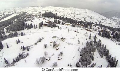 Aerial shot of village in the Carpathian mountains at winter time