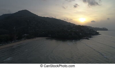 Aerial shot of waves and beautiful sunset on Surin beach in Phuket