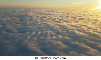 Aerial shot of wavy clouds from a plane window at gorgeous...