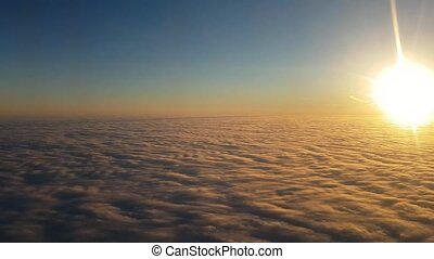 Aerial shot of yellow and blue clouds from flying plane at sunset in summer