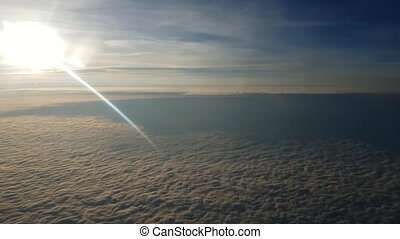 Aerial shot of yellow and blue clouds from plane window at sunset in summer