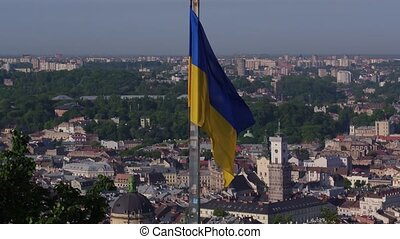 Aerial Shot Ukrainian Flag Flying on Top of the Beautiful Panorama of the City Lviv.