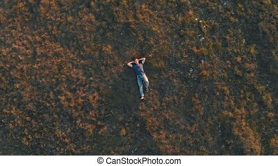 Aerial shot young man lying down and resting - Aerial shot...