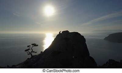 AERIAL SILHOUETTE: young woman climbs up a mountain. Lady reaching the summit in beautiful scenery.