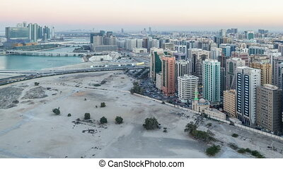Aerial skyline of Abu Dhabi city centre from above day to night timelapse