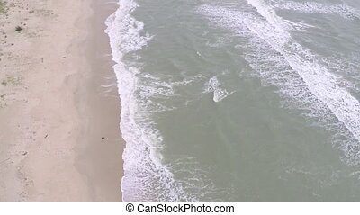 Aerial slow motion shot of sea tide on a sandy beach