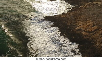 Aerial. Slow motion video of waves at sunset.