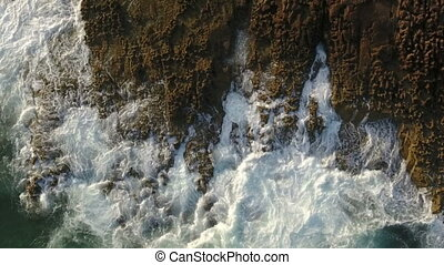 Aerial. Slow motion waves splashing on the rocks, view from...