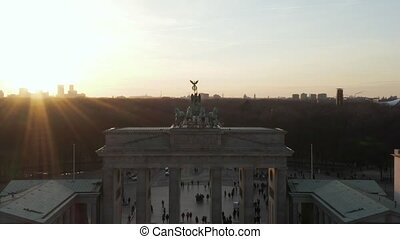 AERIAL: Slowly approaching Brandenburg Gate and Tiergarten in beautiful sunset sunlight with close view on Quadriga Green Statue in Berlin, Germany 4K