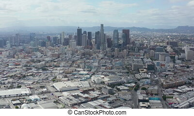 AERIAL: Slowly Circling Downtown Los Angeles Skyline with Warehouse Art District in Foreground with Blue Sky and Clouds 4K