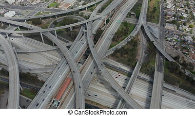 AERIAL: Slowly Circling over Judge Pregerson Huge Highway Connection showing multiple Roads, Bridges, Viaducts with little car traffic in Los Angeles, California on Beautiful Sunny Day
