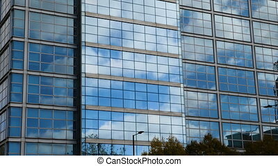 AERIAL. Smooth camera movement in front of office building windows reflecting sunny blue sky with white puffy clouds. 4k