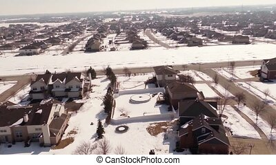 Overhead aerial view of residential houses and yards along suburban street covered in snow - Travel and leisure concept