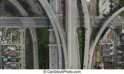 AERIAL: Spectacular Overhead follow Shot of Judge Pregerson Highway showing multiple Roads, Bridges, Viaducts with little car traffic in Los Angeles, California on Beautiful Sunny Day
