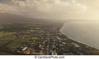 Aerial sun cityscape at ocean bay. Urban streets with houses at green valley. Tropic nature landscape at sea shore. Summer vacation scenic at sunny day with mist. Sun flare reflection at water surface