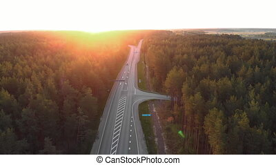 Aerial sunrise shot of road outside city in a countryside forest with cards and trucks passing buy - Follow vehicle shot - Top view from above