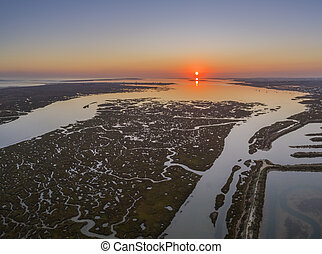 Aerial sunset seascape in Ria Formosa wetlands natural park,...