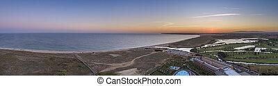 Aerial sunset seascape of Salgados beach and lagoon in Albufeira, Algarve tourism destination region, Portugal.