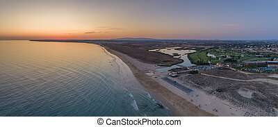 Aerial sunset seascape of Salgados beach in Albufeira, Algarve tourism destination region, Portugal.
