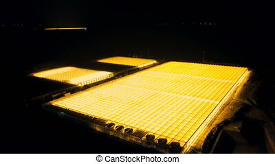 Aerial survey of luminous greenhouses - Flight at night over...