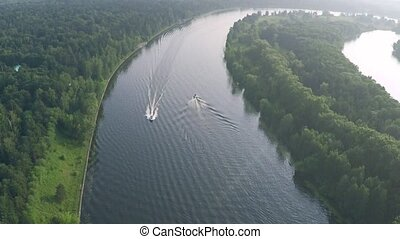 Aerial tilt shot of two motorboats cruising along the river