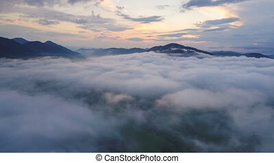 Aerial time lapse flight above mist clouds over beautiful evening nature colors hyperlapse