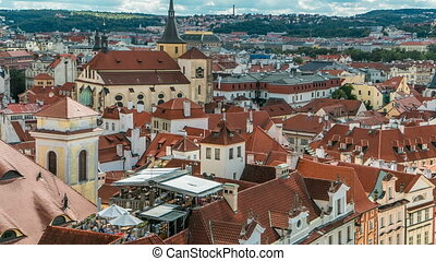 Aerial timelapse view of the traditional red roofs of the city of Prague, Czech Republic with the church of St. Jilji