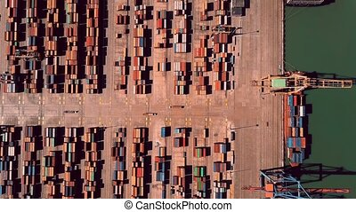 Aerial top-down hyperlapse of busy seaport container...