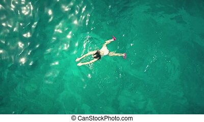Aerial top down rising shot of a young woman swimming in the...
