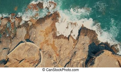Aerial top down shot of sea surf and ancient castle ruins on the rock