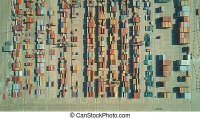 Aerial top down time lapse of busy seaport container yard -...