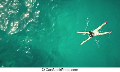 Aerial top down view of a beautiful young woman swimming in...