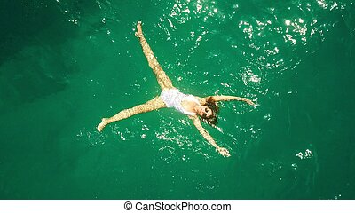 Aerial top down view of a beautiful young woman in a white swimsuit bathing in the sea