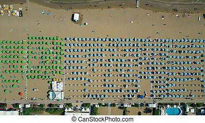 Aerial top down view of a big crowded sandy beach in Italy. Summer vacation time