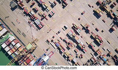 Aerial top down view of a cargo ship and seaport container yard