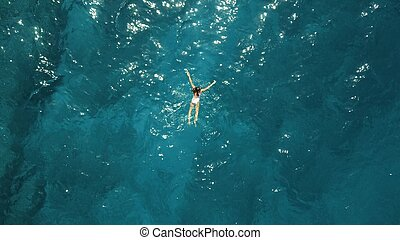Aerial top down view of a girl in a white swimsuit swimming in the blue sea