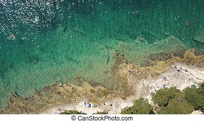 Aerial top down view of a rocky beach of the Adriatic sea. Summer vacation time