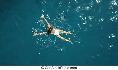 Aerial top down view of a young woman in a white swimsuit swimming in the sea