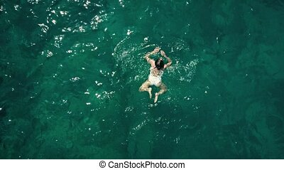 Aerial top down view of a young woman swimming in the sea -...