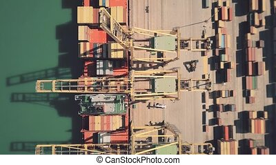 Aerial top down view of big cargo ship being unloaded at...