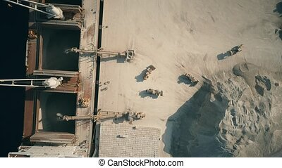 Aerial top down view of bulk carrier ship and cement loaders...