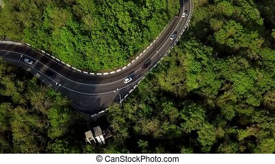 Aerial top down view: of cars driving on zig zag winding...
